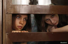 "Nadezhda Tolokonnikova (L) and Maria Alyokhina, members of female punk band ""Pussy Riot"", look out from the defendent's cell in a courtroom in Moscow July 30, 2012."