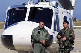 Lebanese army soldiers stand guard in front of a military Huey II helicopter during a ceremony at the Rafik Hariri International Airport in Beirut, Lebanon, March 31, 2016. T