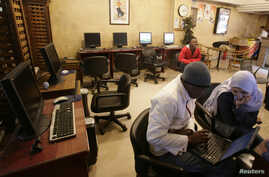 FILE - People sit in an internet cafe in Cairo, Feb. 3, 2008.