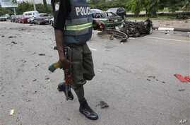 A Nigerian police officer walks past the burnt out shell of a car, after a car bomb exploded in Abuja, Nigeria, 1 Oct  2010