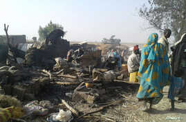 People return to the site after a bombing attack of an internally displaced persons camp in Rann, Nigeria Jan. 17, 2017.