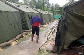 FILE - A man walking between tents at Australia's regional processing centre on Manus Island, in Papua New Guinea.