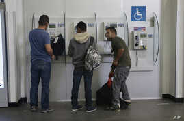FILE - Mexican citizens use pay phones at the airport after being deported from the U.S., in Mexico City, Feb. 23, 2017.