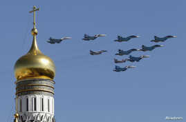 Russian military planes fly above the Kremlin, with the Ivan the Great Bell Tower seen in the foreground, during the Victory Day parade in Moscow's Red Square, May 9, 2014.
