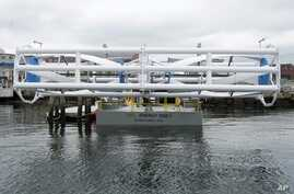 FILE - The Energy Tide 2, the largest tidal energy turbine ever deployed in the U.S., appears on a barge  in Portland, Maine, June 13, 2011.