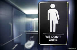 FILE -- A sign protesting a recent North Carolina law restricting transgender bathroom access is seen in the bathroom stalls at the 21C Museum Hotel in Durham, North Carolina May 3, 2016.