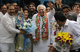 Congress party leader Kapil Sibal, center and his wife Promila Sibal flash victory signs as supporters present them with flower bouquets after Sibal filed his nomination papers for the upcoming parliamentary elections in New Delhi, India, March 20, 2