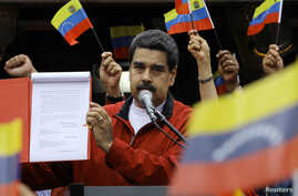 """Venezuela's President Nicolas Maduro shows a document with the details of a """"constituent assembly"""" to reform the constitution during a rally at Miraflores Palace in Caracas, Venezuela, May 23, 2017."""