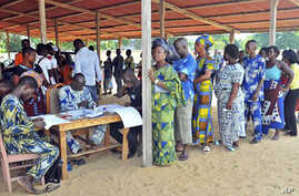 Men and women stand in line to cast their ballots at the city of Cotonou, Benin, March 13, 2011