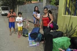 Residents wait for a truck to transport them into an evacuation center as local officials ordered enforced evacuation ahead of Typhoon Bopha in Cagayan de Oro City, southern Philippines, December 3, 2012.