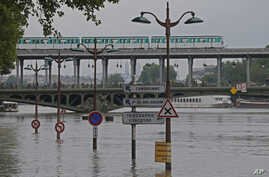 Road signs emerge on the banks of the Seine river next to the Bir Hakeim bridge during floods in Paris, France, June 4, 2016.