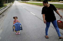 Rosemary Acevedo-Gonzalez, right, walks with her daughter Jordalis, 2, who asked to carry her own clothing after retrieving it upon returning to their home for the first time since it was flooded in the aftermath of Hurricane Florence in Spring Lake,
