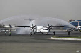 In this photo provided by Tasnim News Agency, a traditional water cannon salute welcomes an Iran Air's new commercial aircraft at Mehrabad airport in Tehran, Aug. 5, 2018.