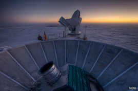 The sun sets behind BICEP2 (in the foreground) and the South Pole Telescope (in the background).