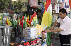FILE - A Kurdish man sells flags of the semi-autonomous region of Kurdistan in his shop in Arbil, 310 km (193 miles) north of Baghdad, August 30, 2009.