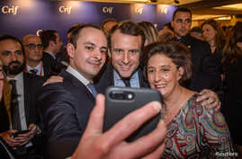 Emmanuel Macron, center,  candidate for the 2017 French presidential election poses for a selfie with guests during the annual dinner of the Representative Council of France's Jewish Associations in Paris, Feb. 22, 2017.