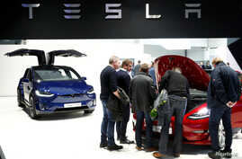 Visitors inspect Tesla electric cars at Brussels Motor Show, Belgium, Jan. 18, 2019.