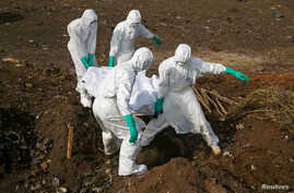 Health workers carry the body of a suspected Ebola victim for burial at a cemetery in Freetown, Sierra Leone, Dec. 21, 2014.
