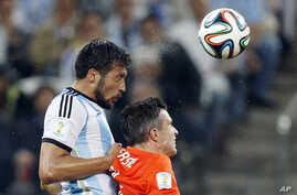 Argentina's Ezequiel Garay, left, and Netherlands' Robin van Persie go for a header during the World Cup semifinal soccer match between the Netherlands and Argentina at the Itaquerao Stadium in Sao Paulo, Brazil, July 9, 2014.