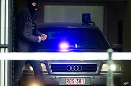 A Belgian policeman leaves a court building with a vehicle believed to be transporting Salah Abdeslam, the top suspect in last year's deadly Paris attacks, who appeared before a judge in Brussels, Belgium,  March 24, 2016.