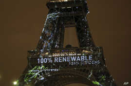 FILE- Artwork entitled 'One Heart One Tree' by artist Naziha Mestaoui is displayed on the Eiffel tower ahead of the 2015 Paris Climate Conference, in Paris. The Paris Agreement on climate change cams into force Nov. 4, 2016, after a year with remark