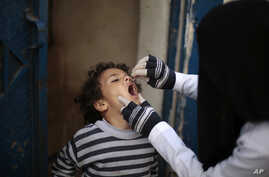 A Yemeni health worker administers a dose of polio vaccine to a boy during a house-to-house immunization campaign in Sana'a, Yemen, Feb. 21, 2017.