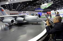 FILE - A foreign visitor takes a photo of a model of Y-20 military transporter aircraft at Aviation Industry Corporation of China (AVIC)'s booth at the Aviation Expo China 2015, in Beijing, Sept. 16, 2015.