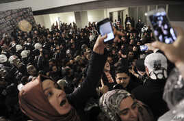 Journalists react as riot police enter the headquarters of Turkey's largest-circulation newspaper Zaman in Istanbul, March 4, 2016. The police raid came hours after a court placed it under the management of trustees on Friday.