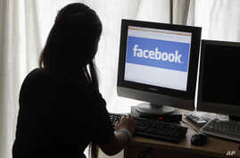 FILE - A girl looks at Facebook on her computer in Palo Alto, California.