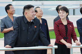 North Korean leader Kim Jong Un (2nd L) and a woman being identified by state TV as his wife 'Comrade Ri Sol Chu,' visit the Rungna People's Pleasure Ground, which is nearing completion, in Pyongyang, July 25, 2012.