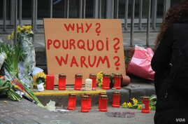 A placard outside one of the entrances to the Maelbeek metro station asks 'why' while other writing expresses calls for both peace and anger in Brussels, Belgium, March 24, 2016. (H. Murdock/VOA)