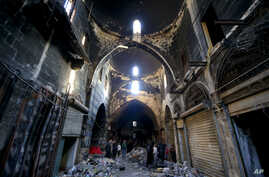 FILE - Syrians walk amid the destruction, in the Old City of Aleppo, Syria.