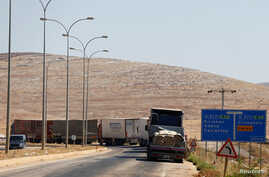Commercial Turkish trucks wait to cross to Syria near the Cilvegozu border gate, located opposite the Syrian commercial crossing point Bab al-Hawa in Reyhanli, Hatay province, Turkey, Sept. 16, 2016.