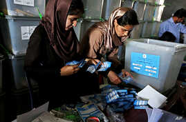 Afghan election commission workers sorts ballot papers for an audit of the presidential run-off votes at a election commission office in Kabul, July 18, 2014.
