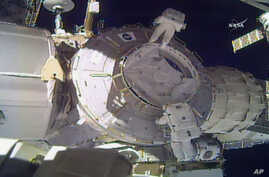 In this image made from video provided by NASA, U.S. astronauts Peggy Whitson, above, and Shane Kimbrough work on the outside of the International Space Station, March 30, 2017.