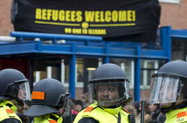"FILE - Two demonstrators carry a banner reading ""Refugees Welcome"" as Dutch riot police separates them from an anti-islam Pegida demonstration in Amsterdam, Netherlands, Saturday, Feb. 6, 2016."