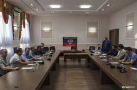 FILE - Representatives of pro-Russia separatists, Kyiv, Moscow and the OSCE are seen at initial talks in Ukraine's eastern city of Donetsk June 23, 2014.