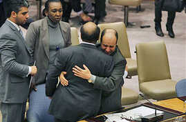 Libya's deputy UN ambassador Ibrahim Dabbashi, right, hugs Libya's UN ambassador Mohamed Shalgham after a meeting of the Security Council at United Nations headquarters in New York, February 25, 2011