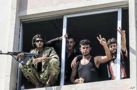 FILE -- In this Aug. 31, 2016, photo, Free Syrian Army fighters give the victory sign, in Jarablus, Syria. Veteran Syrian rebels who have fought Assad for years are struggling to find a place in a bewildering battlefield where several wars are all be