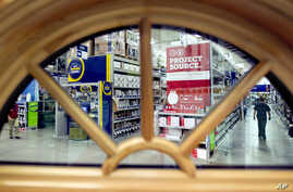 FILE - A shopper is seen through a window on display at a Lowe's store in Atlanta. The U.S. economy grew at the fastest pace in two years in Q3 2016, driven by businesses making purchases to restock shelves and rising exports.