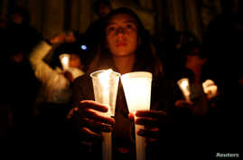 """A supporter of the peace deal signed between the government and the Revolutionary Armed Forces of Colombia (FARC) rebels holds candles while attending a gathering at Bolivar Square during a """"Silent March"""" in Bogota, Colombia, Oct. 5, 2016."""