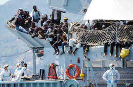 """Migrants wait to disembark from the Italian Navy vessel """"Chimera"""" in the harbor of Salerno, Italy, April 22, 2015. Italy pressed the European Union on Wednesday to devise concrete steps to stop the deadly tide of migrants on smugglers' boats in the M"""