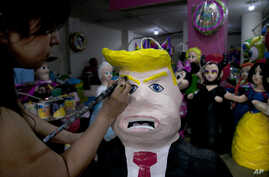 "FILE - Alicia Lopez Fernandez paints a pinata depicting Donald Trump at her family's store ""Pinatas Mena Banbolinos"" in Mexico City, July 10, 2015. In a surprise move, Donald Trump will travel to Mexico Aug. 31 to meet with President Enrique Pena Nie"