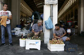 Two street vendors talk each other outside the main fish market of Athens, Aug. 20, 2018, on the day that Greece's eight-year crisis will be officially over.