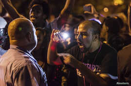 A demonstrator confronts a police officer in St. Louis, Missouri, Oct. 8, 2014, during protests following an incident in which a white off-duty policeman shot and killed a black teenager.