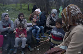 Stranded in the northern Greek border station of Idomeni for 15 days, Syrian refugees sit next to a fire as they wait to be allowed to cross to Macedonia, March 5, 2016.