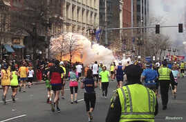 Runners continue to run towards the finish line of the Boston Marathon as an explosion erupts near the finish line of the race in this photo exclusively licensed to Reuters by photographer Dan Lampariello after he took the photo in Boston, Massachuse