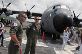"FILE - Members of the flight crew stand in front of the U.S. Air Force Reserve's ""Hurricane Hunter"" WC-130J aircraft at Panama Pacifico Airport, at an exhibition during its Caribbean Hurricane Awareness Tour, in Panama City, Panama, April 26, 2018."