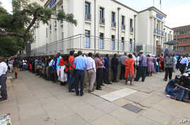 In this photo taken on Tuesday, May, 3, 2016, Zimbabweans wait in a long line to withdraw cash in Harare. Severe shortages of U.S dollars that are used as  local currency have forced many residents into cash hunter-gatherers.