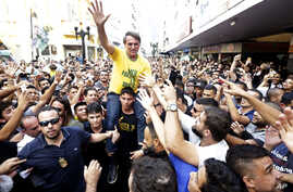Presidential candidate Jair Bolsonaro is taken on the shoulders of a supporter moments before being stabbed during a campaign rally in Juiz de Fora, Brazil, Aug. 6, 2018.